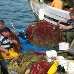 Pescatori intenti a riparare reti per la pesca da posta