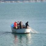 Pescatori intento a salpare reti da posta