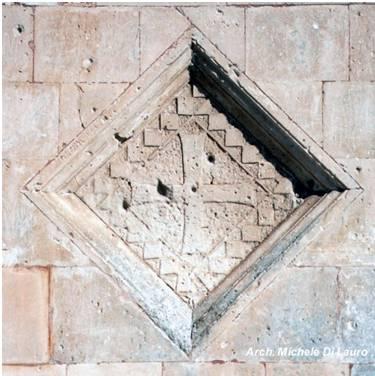Fig. 1 Santa Maria di Siponto Croce templare posta sulla facciata Nord, quella con il protiro d'ingresso del tardo Duecento. La croce è circondata dai riquadri di una scacchiera, altro simbolo templare.