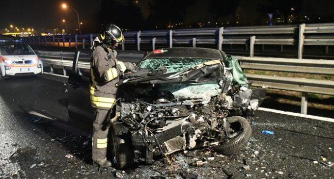 Un vigile del fuoco accanto a una delle auto coinvolte in un incidente stradale avvenuto lungo la tangenziale est di Milano e che sarebbe stato causato da un'auto entrata in contromano, 26 gennaio 2019.